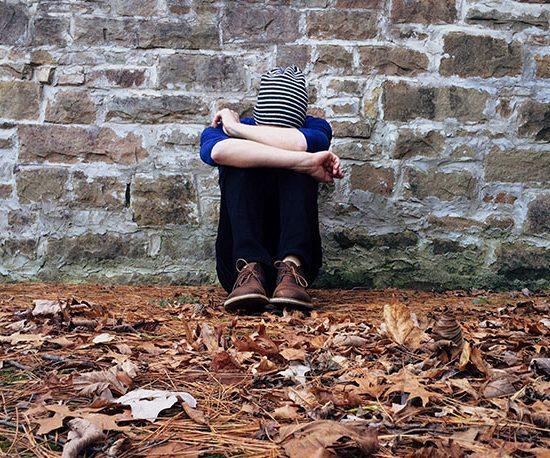 Person sitzt zusammengekauert und mit gesenktem Kopf vor einer Steinmauer