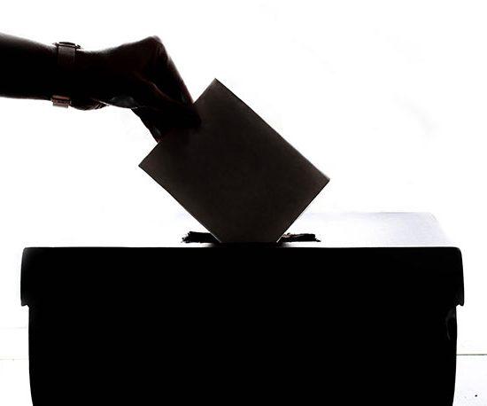 Eine Person wirft einen Umschlag in eine Wahlurne.