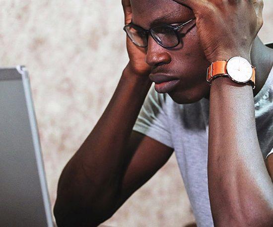 Person vor Laptop mit über dem Kopf zusammengeschlagenen Händen.
