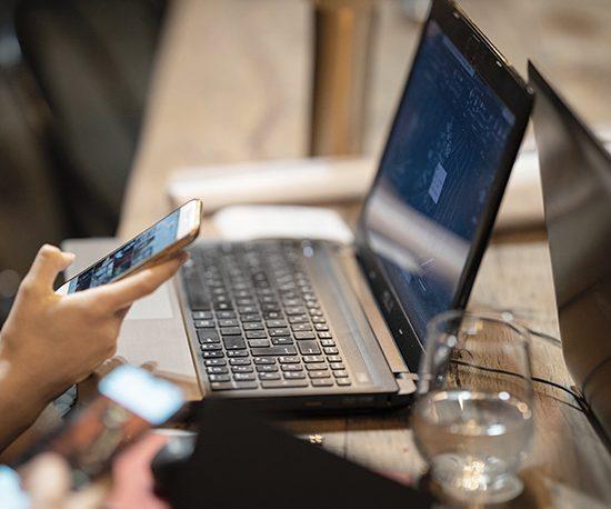 Person mit Smartphone in der Hand sitzt vor einem Laptop.