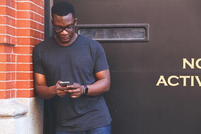 Person steht vor einer Ziegelsteinwand und blickt auf ihr Smartphone