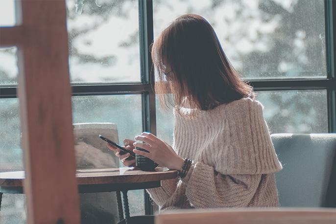 Person mit Smartphone sitzt vor einer Fensterfront.